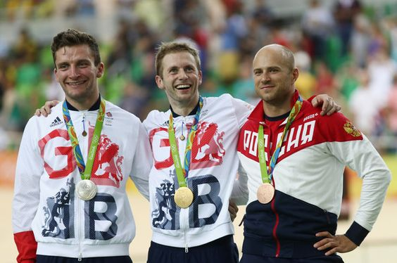 Silver medalist Callum Skinner of Great Britain, gold medalist Jason Kenny of Great Britain and bronze medalist Denis Dmitriev of Russia pose for photographs on the podium at the medal ceremony for Men's Sprint on Day 9 of the Rio 2016 Olympic Games at the Rio Olympic Velodrome on August 14, 2016 in Rio de Janeiro, Brazil.