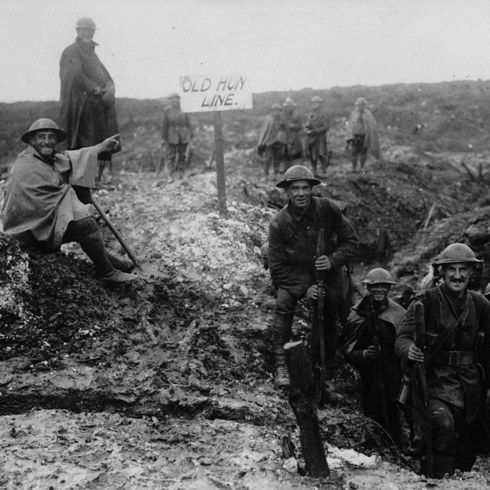 "British soldiers enjoy possession of a newly captured German trench, pointing to a sign which says ""Old Hun Line""."