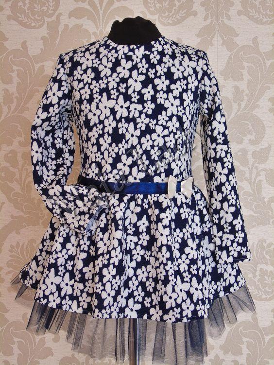 Wyjątkowa sukienka Kwiatuszek wykonana z granatowej dziarniny w białe kwiaty. Dół kreacji wykonany z tiulu, odszytego podszewką. Sukienka posiada długi rękaw oraz kryty zamek. Atłasowa tasiemka w pasie wiązana z tyłu pozwala na dopasowanie sukienki.