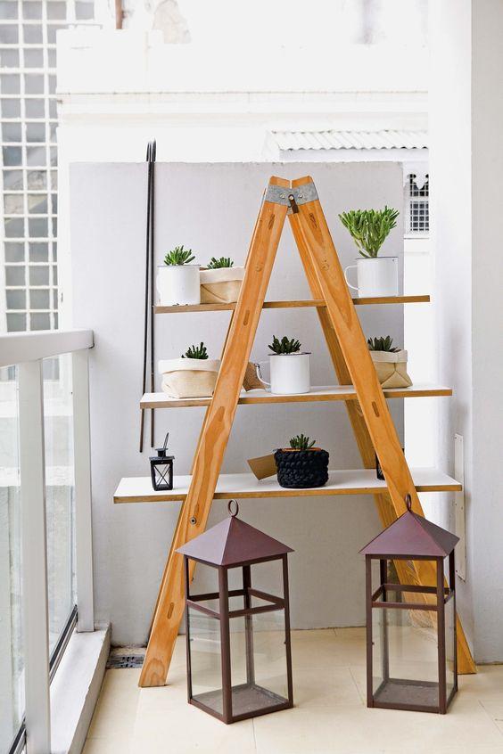 Cómo decorar un monoambiente chico: escalera con estantes hace las veces de biblioteca o repisa para plantas en el balcón.