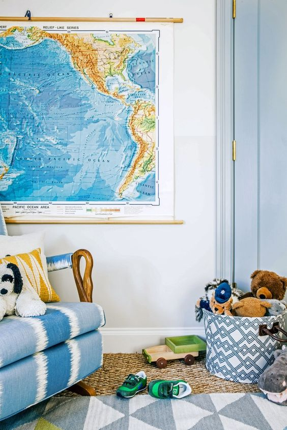 In a corner of the room, a vintage rocking chair belonging to the homeowners was upholstered in a Kravet fabric to give it more modern appeal. A vintage wall map brings in the bright colors that the boys requested, and the cotton rug is by West Elm.