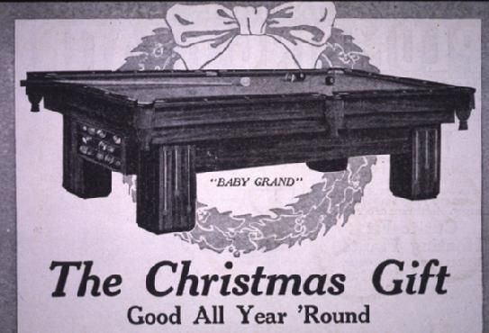 "Some good things just don't change:  The Christmas Gift. Good All Year Round. Brunswick-Balke-Collender advertisement in Popular Mechanics, 1916. It shows a Brunswick ""Baby Grand"" table with a Christmas wreath. The text reads, ""Parents, boys and girls and guests are all fascinated by the royal games of Carom and Pocket Billiards when played on Brunswick tables in cozy home surroundings."""