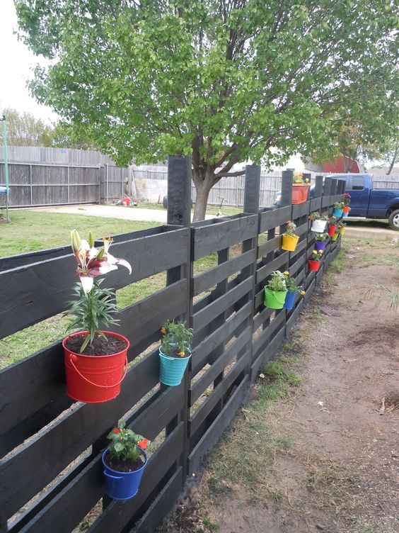 This fence is inexpensive because it's made entirely with pallets. You just pound the stake into the ground and then put the pallets over the top of it and you're ready to go with a privacy fence.