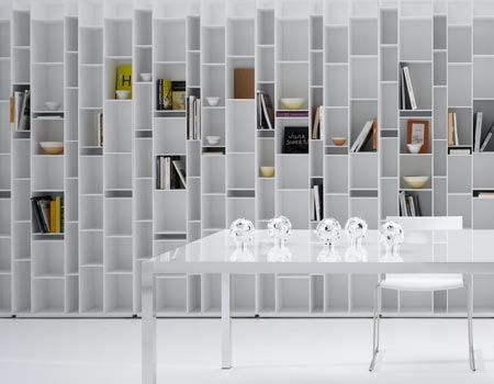 RANDOM  A bookcase made of 6 mm thick MD-wood fibreboards, microgoffered lacquer in black or white. Back of melamine - coated board (thickness 10 mm). Shelves at various standard heights, fit into the backs through concealed slots. Adjustable feet. Ready for wall mounting. By flanking more units, also with the new Random Box or Random Cabinet, large-sized configurations of strong impact can be created.