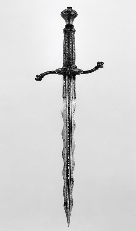 "Parrying dagger (pugnale bolognese), ca. 1550–75; Italian.  Partly gilt steel, brass & wood.  Designed to be used together with a rapier, this dagger is fitted with a side ring, recurved quillons & a depression at the base of one side of the blade to accommodate the thumb and facilitate a firmer grip. The waves in the blade may be intended to act like ""speed bumps"" in breaking the impact of a blow from an opponent's blade. The piercing of the fullers (grooves) is decorative."