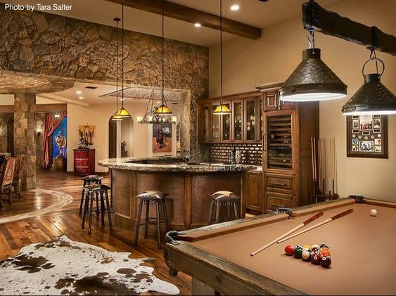 Rustic stone work and exposed beams make this man room a high end masterpiece.