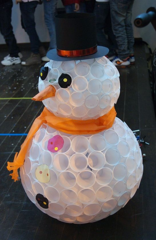 A snowman made with plastic cups.  To make it, staple plastic cups together. They used smaller cups for the head. This is a good idea to do a Christmas balls!