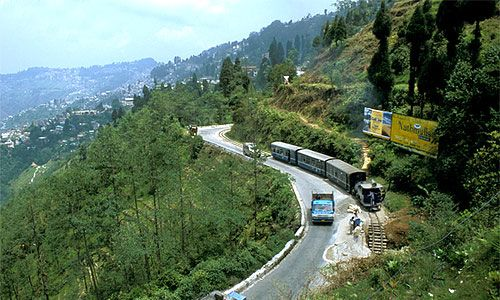 """Darjeeling the dream land of the East. Also called """"Queen of Hills"""", it has been a popular hill station since the British period. Darjeeling is best known as the centre for India's tea trade. It is surrounded by lofty mountains and the view from over the mountains to the snowy peaks of Kanchenjunga and down to the swollen rivers in the valleys are magnificent."""