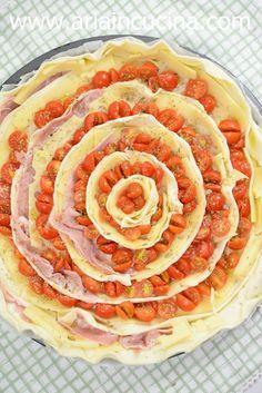 Stendere la pasta sfoglia in uno stampo rotondo foderato di carta forno. Tagliare l'altro rotolo a fettine sottili, di circa un cm Tagliare a listarelle anche il formaggio e il prosciutto cotto, che volendo potete omettere Lavate i pomodorini e tagliateli a metà Ora potete farcire la vostra torta partendo dall'esterno: facendo un cerchio di pomodorini, poi uno di pasta, poi il formaggio, il prosciutto e così via. Spolverare di origano e olio e infornare.