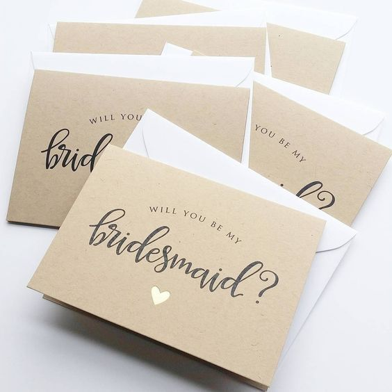 'Will you be my bridesmaid?' folded kraft cards with calligraphy script font and gold foil stamped heart.:
