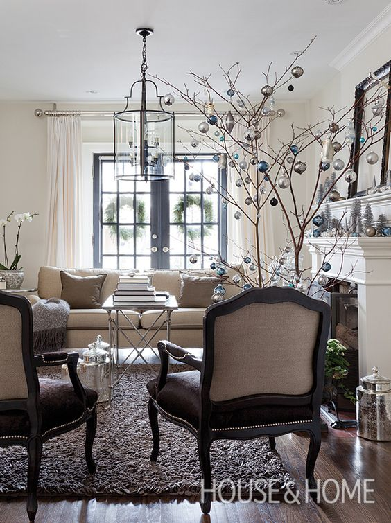 "Designer Ingrid Oomen keeps her living room airy with a pair of dogwood ""trees"" decorated in a strict palette of silver, blue and white. 