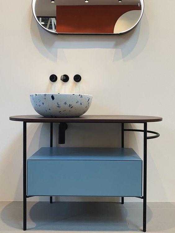 Móvel azul claro, com pernas fininhas e cuba com padronagem de granilite na Ceramica Globo. (Foto: Mariana Conte)