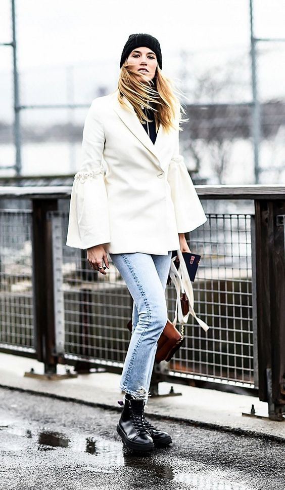 A white blazer is paired with jeans and all-black sneakers
