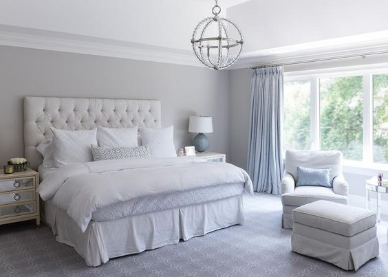 Blue and gray bedroom features a high ceiling accented with a Danville Sphere Chandelier illuminating a white velvet tufted headboard on bed dressed in white and blue bedding flanked by cream mirrored nightstands and blue lamps.