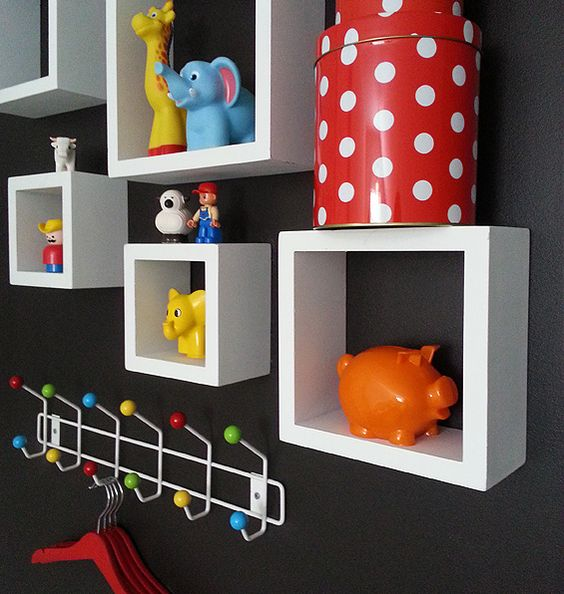 White cube shelves against a wall painted black with lots of bright colored  toys in kids