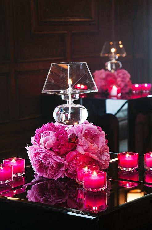 A stunning pomander of hot pink peonies is topped with a glass oil lamp and surrounded by vibrant pink votives.