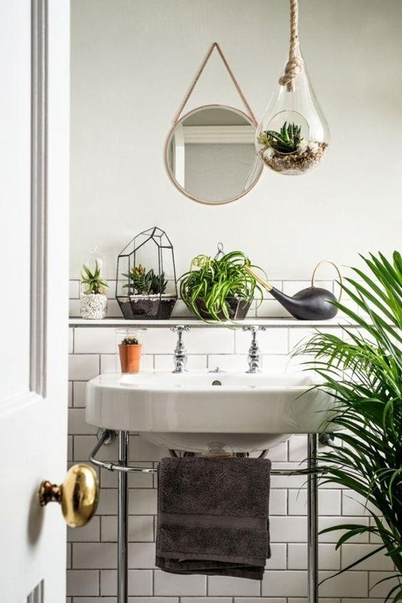 House plants breathe life into interiors, while cleaning the air as they grow, and look amazing and vibrant in any room -- we love the mix of potted succulents, palm trees, air plants and terrariums in this all-white bathroom.:
