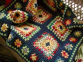 "Beautiful Granny.  Note on the pin when found : ""The variegated yarns in these squares is Red Heart's TLC Essentials. I used three colors: ""sedona"", ""coraline"", and ""island"". For those wanting to do something similar to this I can give you my formula. I kept the center of the large squares the same, blue. Each square has white, and sedona in it. If you keep the white and the red in the large squares you can change out the other yarns. You can see I used some yellows and a pretty mint green."""