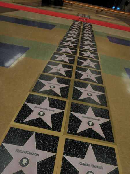 Theme: Let's Make a Movie/ Lights, Camera, Action What to Do: Black construction paper cut in squares, kids can cut out a star, put their names on them, then they can put they're handprints in black on the star. Laminate them and you can tape them to the floor to make it look like Hollywood Boulevard!