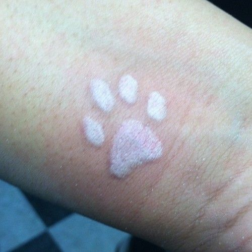 White ink paw print tattoo