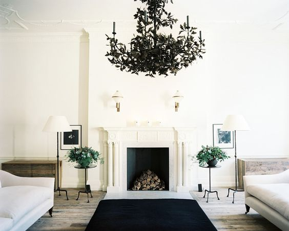 Rose Uniacke - A tole chandelier suspended above a symmetrical seating arrangement
