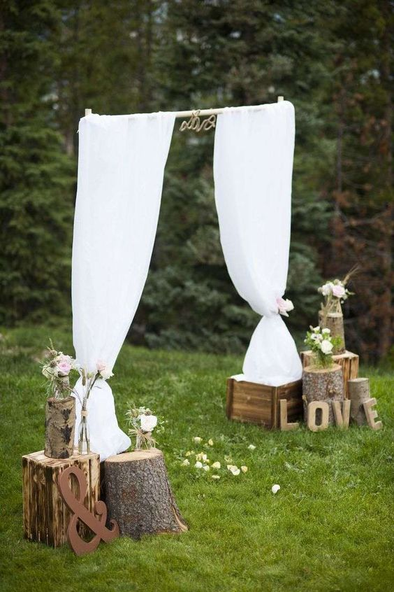 autel de mariage avec voiles blancs, des arrangements de roses dans des vases en écorce