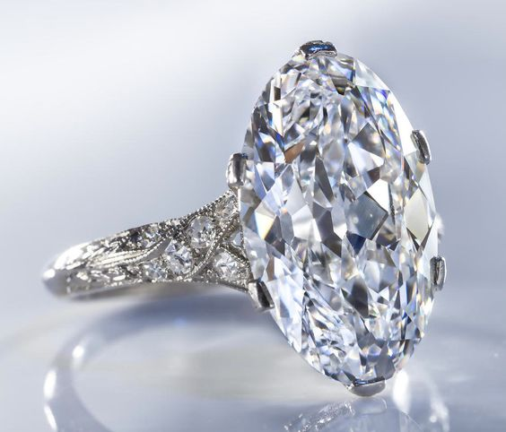 A belle époque diamond solitaire ring, circa 1915  the oval-shaped diamond, weighing 6.98 carats, within a delicate openwork mounting of single-cut diamonds; mounted in platinum