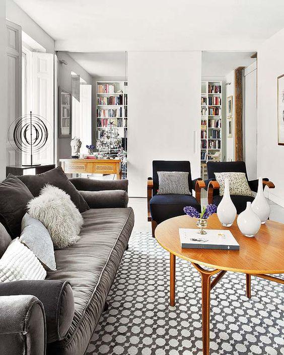 Las diferentes texturas en contraste y los estampados geométricos encajan a la perfección con los muebles de aire retro en esta sala de estar.