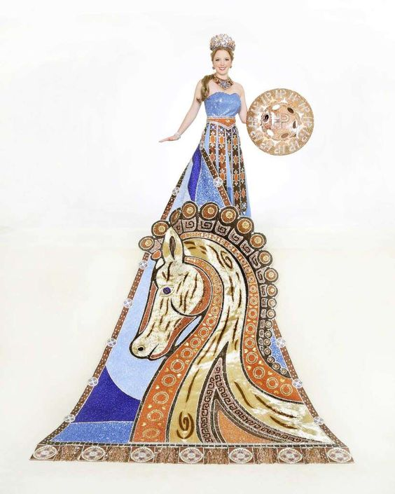 Harrison Alexandra Perkins, Perrin Duchess of Epic Valor. The bold train of gold, copper lamé and brown crushed velvet features the Trojan horse made of thousands of hand-sewn copper, blue, gold and rhinestone beads. The sweetheart neckline dress, a nod to Helen of Troy, is in blue satin, with a bodice beaded with metallic square sequins. She is the daughter of Mr. and Mrs. Harry Allen Perrin. Photo: Courtesy Gary Stanko / Billo Smith Photography: