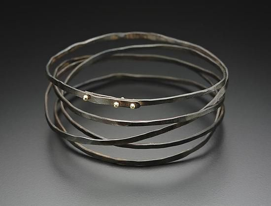 Wrap Bracelet by Peg Fetter. A multi-wrapped bracelet of oxidized steel, with 14k yellow gold accents. Each piece is unique. Placement and patterning of gold accents may vary slightly from that shown, although overall aesthetic of the bracelet will be maintained. Please specify interior circumference size in the box below: 7: