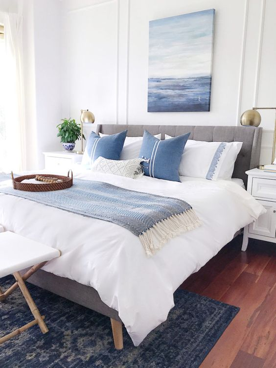 Blue and white calming bedroom decor with coastal artwork