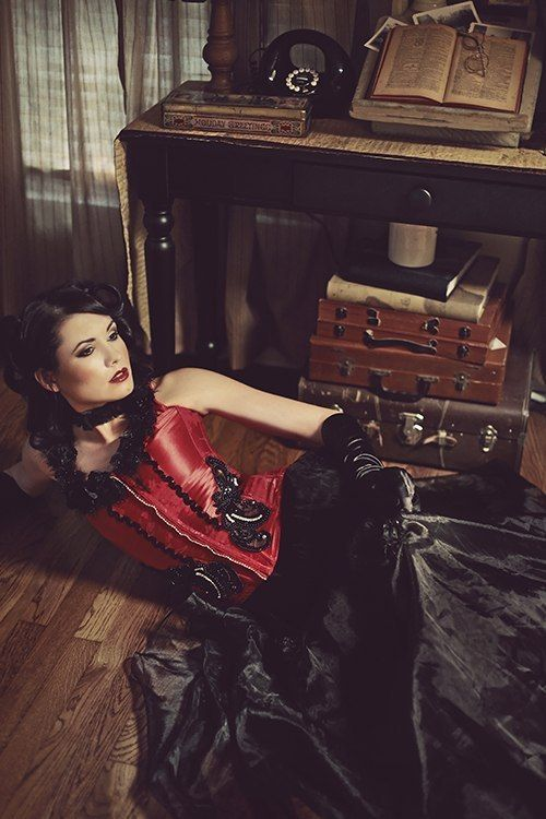 steampunk look: beautiful girl by a vintage desk, wearing crimson satin corset and black satin skirt