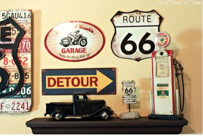 Gallery wall art display in a baby boy's Route 66 nursery theme including vintage road signs, an old, toy pickup truck and a miniature service station gas pump on a shelf