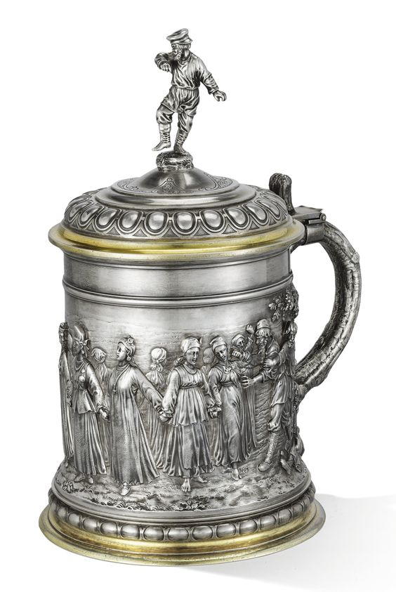 AN IMPRESSIVE PARCEL-GILT SILVER TANKARD, SAZIKOV, MOSCOW, 1873    the body repoussé and chased with a genre scene of a village festival centred with a khorovod of young girls, the domed hinged lid surmounted with a figure of a dancing moujik, the handle formed as a tree bough, gilt interior, 84 standard, French import mark  height: 31cm, 12 1/8 in.