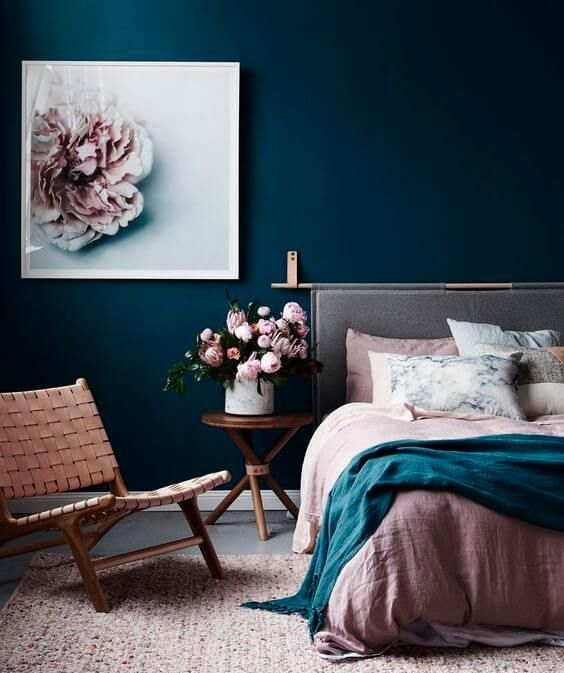 colourful bedroom with dark blue walls and pink details | how to style a bedroom