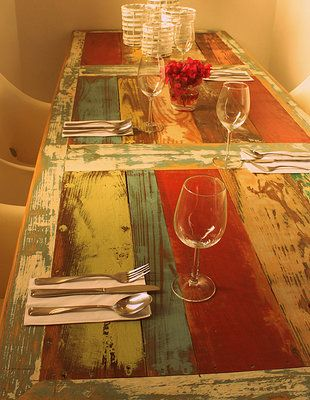 Large colorful diner table, made with reclaimed wood. At Hotel Het Klooster - Curaçao. Designed by Eugene Maduro.