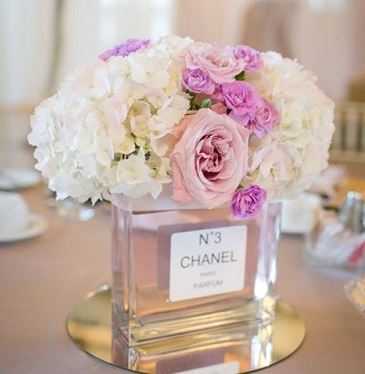Gorgeous idea of using Chanel perfume bottles as vases for flowers, perfect for a Parisian themed wedding or bridal shower.: