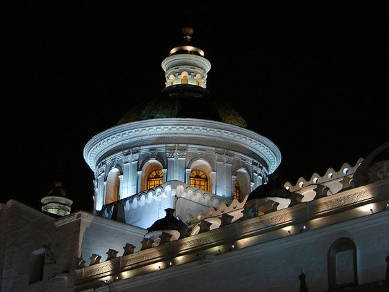 Church dome lighted up by white and yellow lights in the night