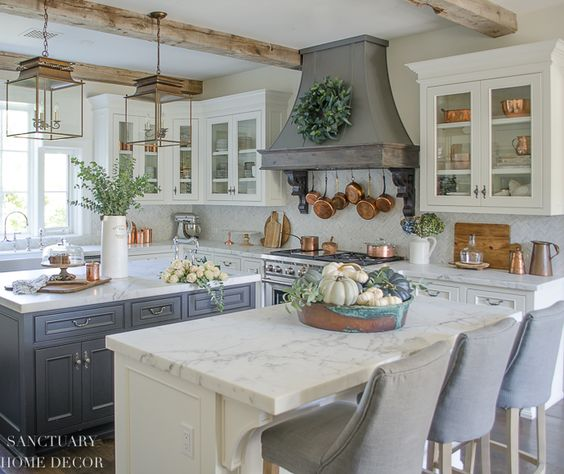 Farmhouse kitchen with fall decorating. Glass front cabinets with copper accents. Range hood with wreath. Copper pots