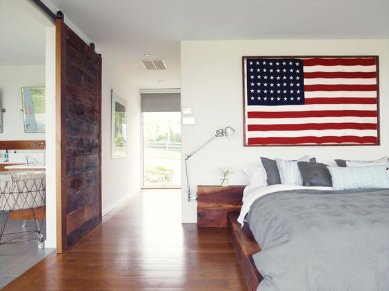 He built the walnut bed and nightstands in the master bedroom with the help of Hannah's two brothers. One of his clients at his hair salon gave him the American flag; the bedside lights are Tolomeo classic wall lamps by Artemide. The bed linens are from Inhabit. A sliding barn door rolls sideways to reveal the bathroom.: