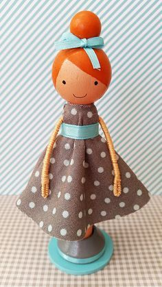 Suzie, a super cute wooden clothespin doll stands just over four inches tall, and is uniquely hand painted in vibrant colors and wears a real otton fabric dress in a gray and light blue polka dot print