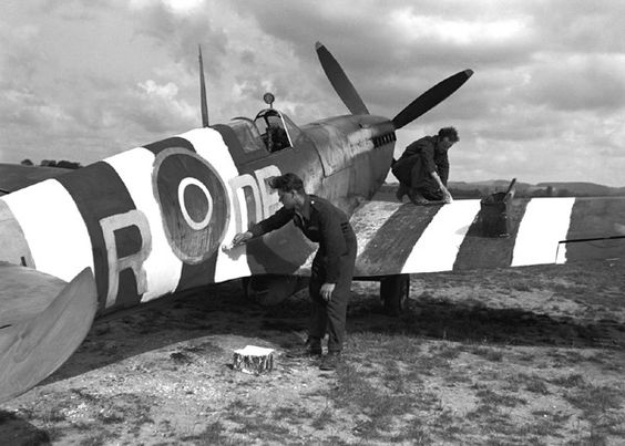 Mechanics paint D-Day colors on Spitfire;