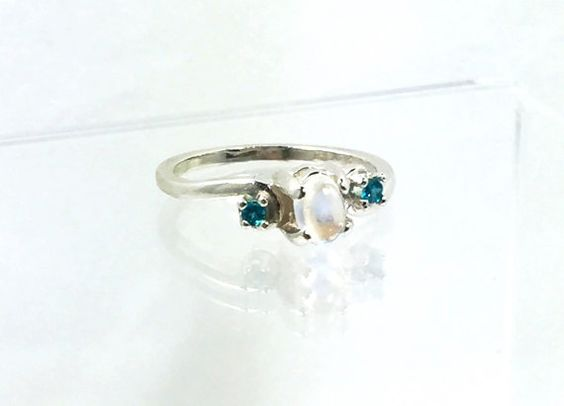 This womens engagement ring features a Blue Moonstone gemstone with Blue Apatite accent stones. The Moonstone is a wonderful choice for a