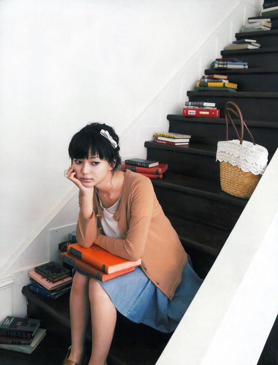 本が置かれた階段に座って頬杖をついている多部未華子の画像