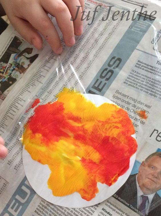 Een zon maken met een rondje papier, rode en gele verf en vershoudfolie.