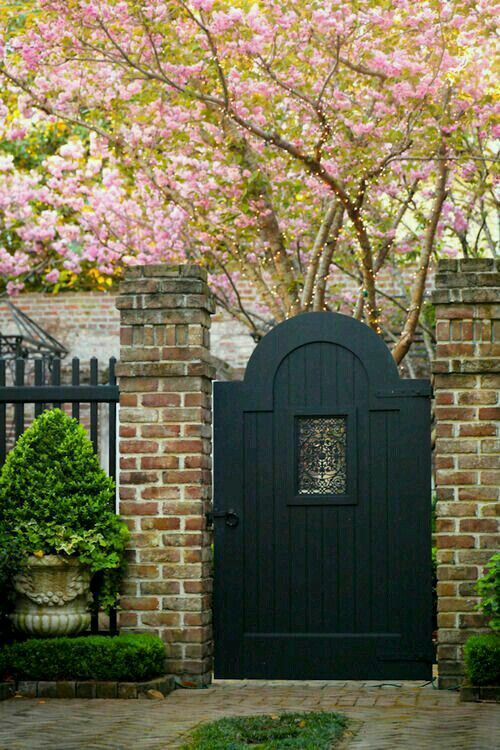 Garden gate inspiration: a dark painted arched door flanked by brick posts leads to a beautiful garden with flowering pink tree. #gardengate #curbappeal #gardeninspiration #spring