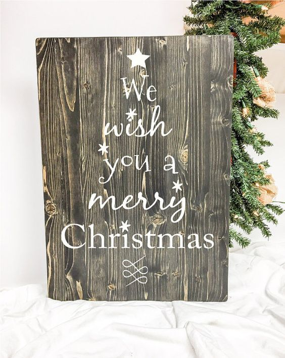 "This cute Christmas themed wood sign features song lyrics from ""We Wish You a Merry Christmas."" This board has plenty of character with the song lyrics being in the shape of a Christmas tree. This sign is pine & measures 16"" w x 24"" h x 3/4 thick. Vinyl letters. Handmade in the USA. We always strive for great customer service. If you have a question or concern about one of our products please don't hesitate to contact us and we will handle it as quickly as possible!  *Please Note*  Wood stai...:"
