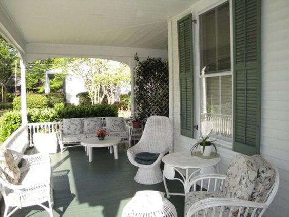 Love these wide white porches with wicker and cane furniture.