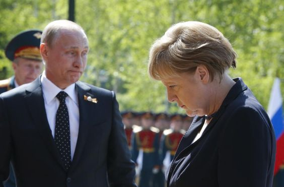 German Chancellor Angela Merkel and Russian President Vladimir Putin attend a flower-laying ceremony at the Tomb of the Unknown Soldier by the Kremlin walls in Moscow, Russia, May 10, 2015. REUTERS/Grigory Dukor