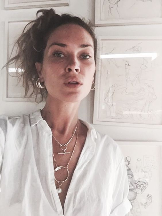 Erin Wasson in a white collared button down and layered necklaces